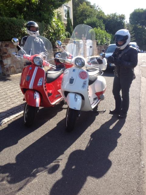 Zwei Menschen in Motorrad-Kluft neben ihren Vespas.