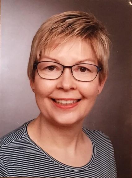Porträt einer Frau mit Brille und kurzen, blonden Haaren.