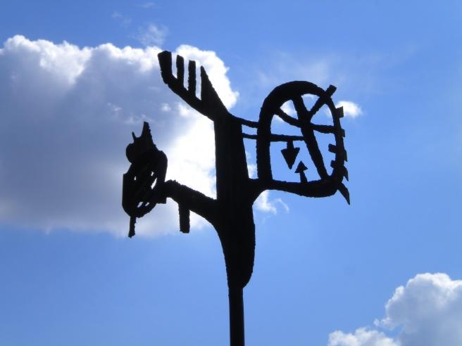 Schwarze Skulptur vor strahlend blauem Himmel