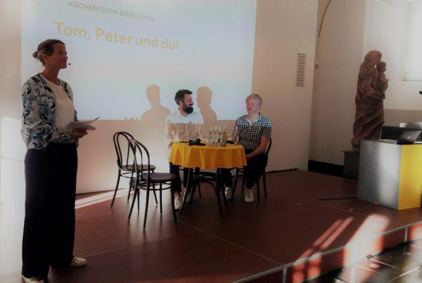Tom Klose und Peter Post am Küchentisch. Daneben die Moderatorin Tina Tunali