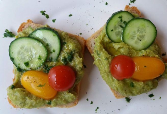 Zwei Scheineb Brot, dick bestirhcne mit Avocadomus und Tomaten